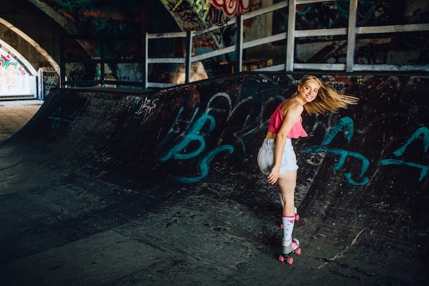 A picture of well-built rollerblaider riding backwards. she is looking back careful. girl is smiling. her hair is waving.