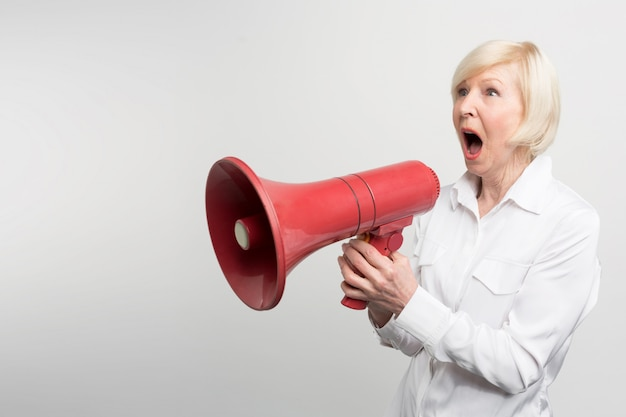 A picture of white-haired woman standing a pronouncing a speech for defencing human rights and support feminists. she is using a speaker for that purpose.