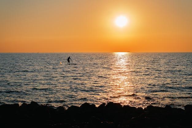 끝없이 펼쳐진 아름다운 바다에서 석양을 바라 보는 알 수없는 서퍼의 작은 실루엣이 그려져 있습니다. 활동적인 건강한 라이프 스타일