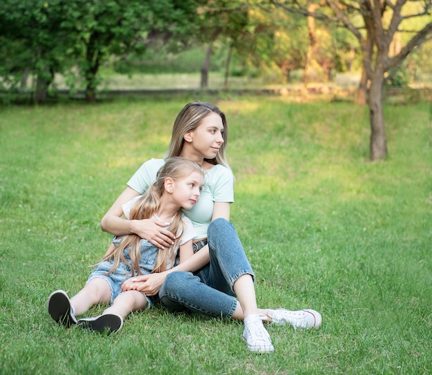 Picture of woman and child sitting on the grass and having fun together