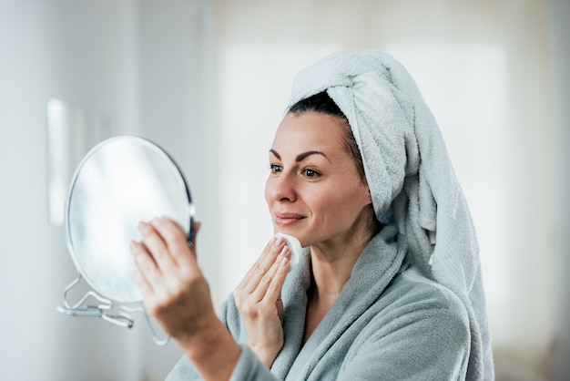 A picture of a woman cleaning her face.