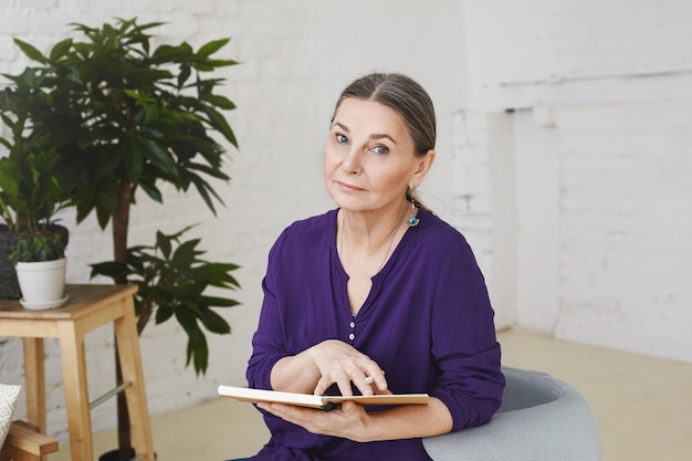 Picture of woman professional psychologist in her fifties waiting for next client, sitting in her modern office on armchair, holding open copybook and looking with serious expression