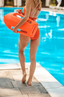 A picture of a woman in a red swimming suite near the pool