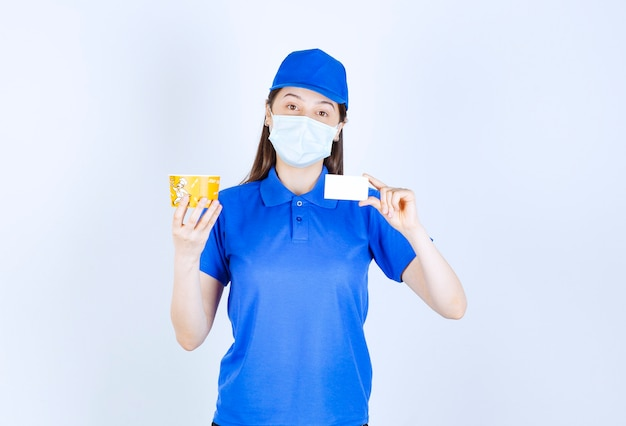 Picture of woman in uniform and medical mask holding card .