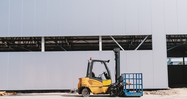 Picture of yellow forklift in front of the grey building.