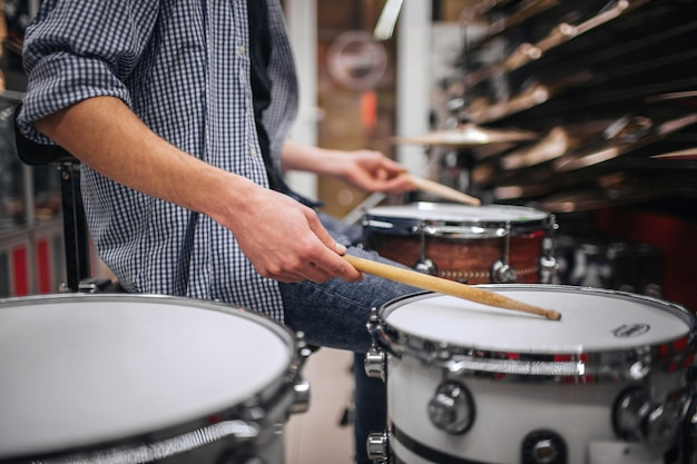 Picture of young bearded man playing on drus. he touches them with special sticks. many cymbals are above on shelfs. guy is alone in room.