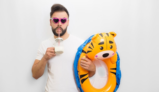 Picture of young bearded man standing and chilling. he drinks milk and hold kids matrass in hand. guy wears sunglasses. he looks confident. isolated on white  .
