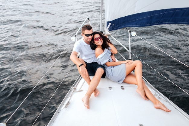 Picture of young and beautful couple sitting and lying on yacht bow. they wear sunglasses. she looks on camera and posing. brunette smiles. he sits with legs crossed and looks forward