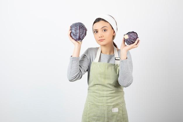 Immagine di una giovane e bella casalinga che tiene in mano due cavoli viola