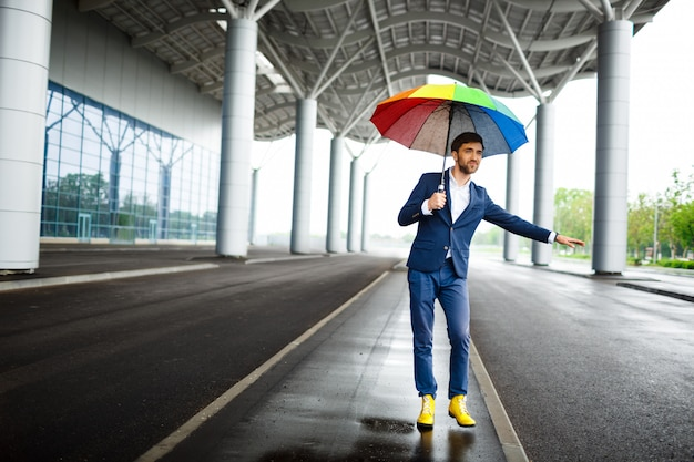 Immagine di giovane uomo d'affari che tiene ombrello eterogeneo che prende l'automobile all'aeroporto