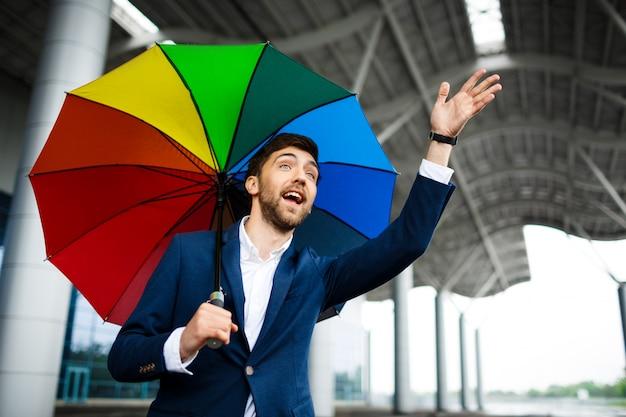 Immagine di giovane uomo d'affari che tiene la mano d'ondeggiamento dell'ombrello eterogeneo Foto Gratuite
