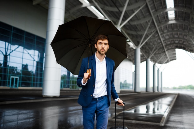 Picture of  young  businessman holding  suitcase and umbrella standing at rainy station