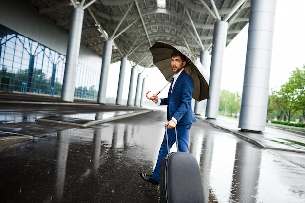 Picture of  young  businessman holding  suitcase and umbrella walking at rainy station