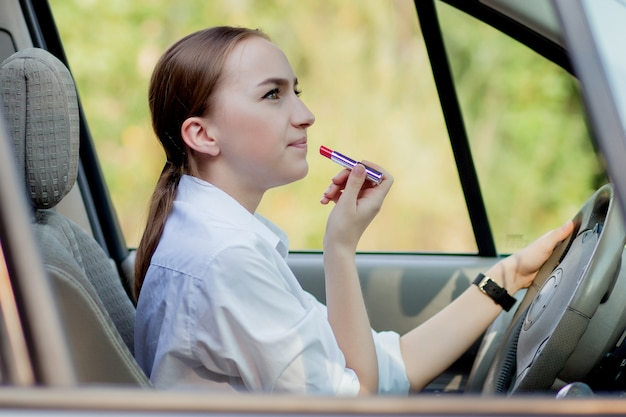 Picture of young businesswoman doing makeup while driving a car in the traffic jam