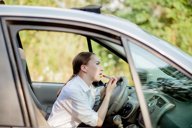 Picture of young businesswoman speaks by phone and doing makeup while driving a car in the traffic jam