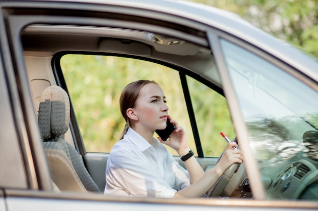 Picture of young businesswoman speaks by phone and doing makeup