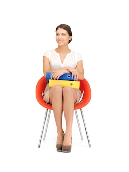 Picture of young businesswoman with folders sitting in chair
