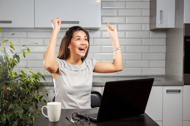 Picture of young female entrepreneur using a laptop while raising hands up and celebrating her success