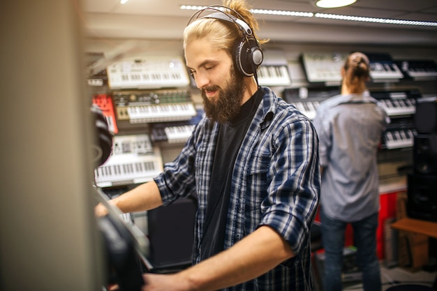 Picture of young guy stand and listens to music through headphones