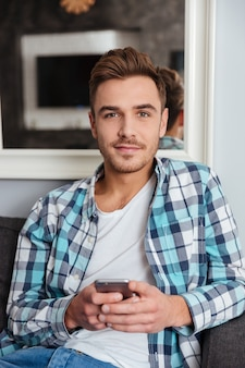 Picture of young handsome man dressed in shirt in a cage print sitting on sofa in home and looking at camera while chatting by phone.