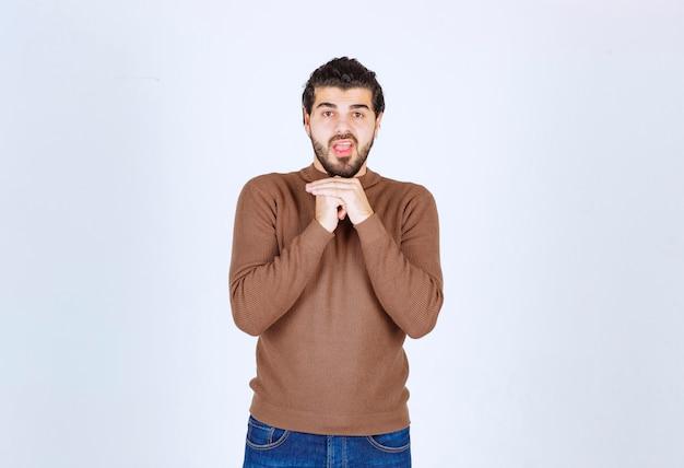 Immagine di un modello di giovane uomo bello in piedi e in posa sul muro bianco. foto di alta qualità