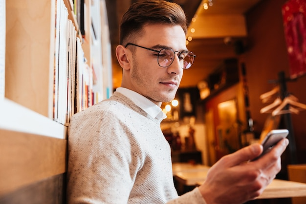 Picture of young handsome man wearing glasses sitting in cafe while using mobile phone.