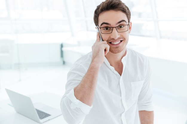 Picture of young happy man dressed in white shirt talking by phone. looking at camera.