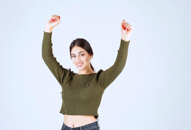 Immagine di un modello di giovane donna felice in piedi e alzando le mani.