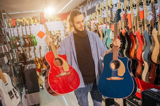 Picture of young hipster stand and hold two colorful acoustic guitars. they are red and dark-blue colors. guy look at second one. man electric guitars are behind him.