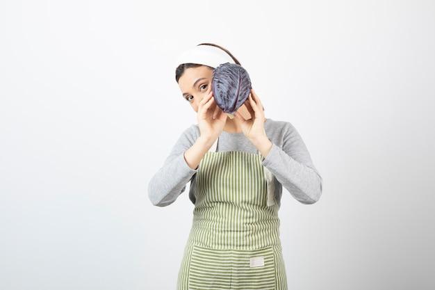 Immagine di una giovane casalinga che mostra cavolo viola su bianco