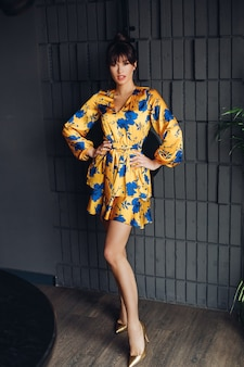 Picture of young lovely caucasian female with dark hair in yellow and blue dress, gold shoes shows different poses for the camera