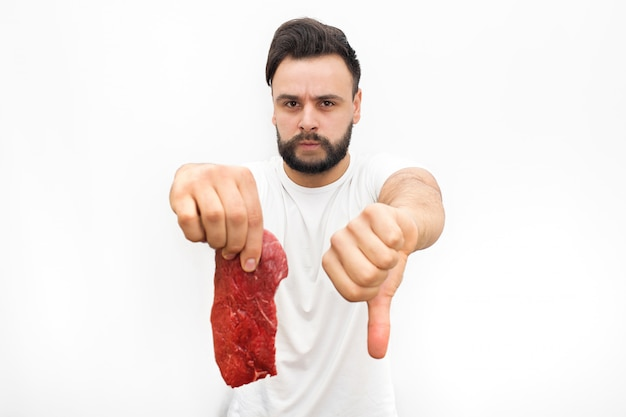 Picture of young man holding bad piece of meat in hand. he shows big thumb down. guy is angry and upset. he looks.