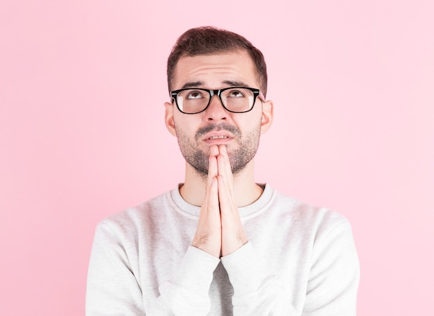 Picture of young man isolated on pink background, having put hands together in prayer, wishing dreaming and waiting for all best