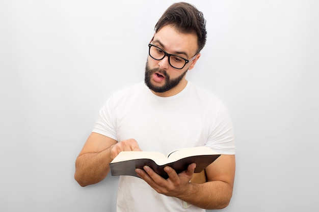 Picture of young man reading aloud from book. he holds it in hands and points on it. young man is concentrated.