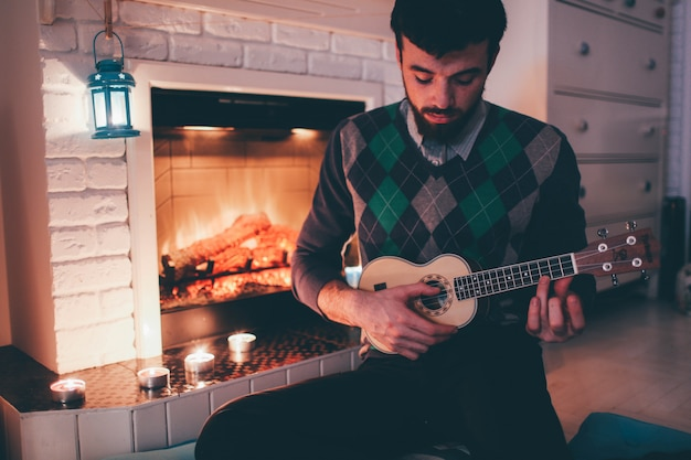 Picture of young man sitting at fireplace and playing ukulele