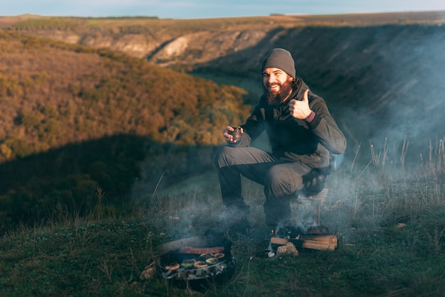 Picture of a young man with beard is sitting near a grill with vegetables and sausages on a field in the morning