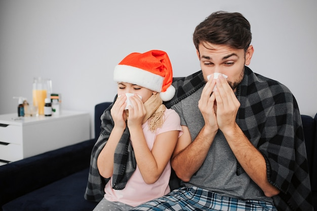 Picture of young man with daughter sitting on sofa and sneezing. they caught cold. flu and sickness. celebrating new year of christmas. red hat of girl's head. festive month