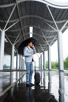 Immagine di giovane uomo d'affari dai capelli rossi che tiene ombrello nero in pioggia e che parla sul telefono