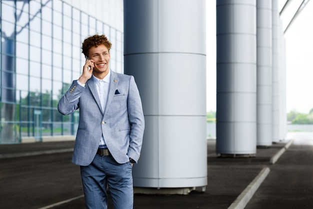 Picture of young redhaired businessman talking on phone smiling
