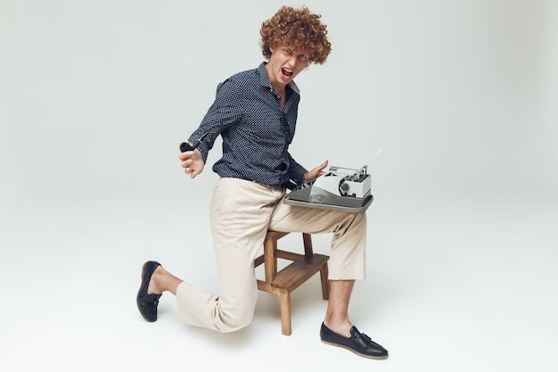 Picture of young screaming angry retro man dressed in shirt sitting and posing isolated. looking camera with pipe holding typewriter.