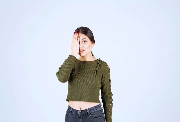 Picture of a young shocked woman model covering an eye with a hand.