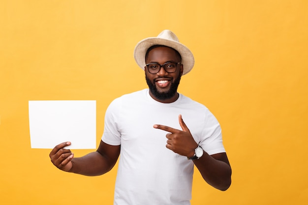 Picture of young smiling african-american man holding white blank board and pointing on it