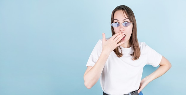 Picture of young surprised female isolated on blue background wearing blue eyeglasses, covers her mouth with the right hand