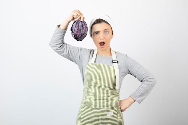 Immagine di una giovane casalinga sorpresa che mostra cavolo viola su bianco