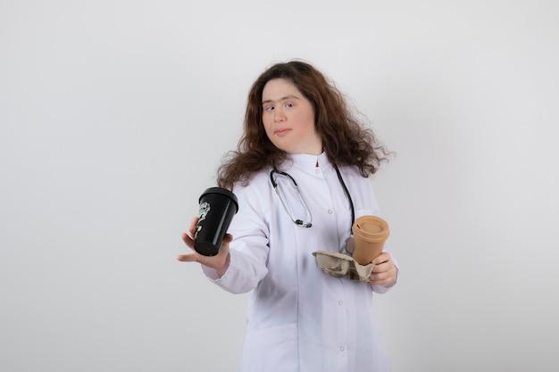 Immagine di un modello di giovane donna in uniforme bianca che tiene un cartone con tazze di caffè.