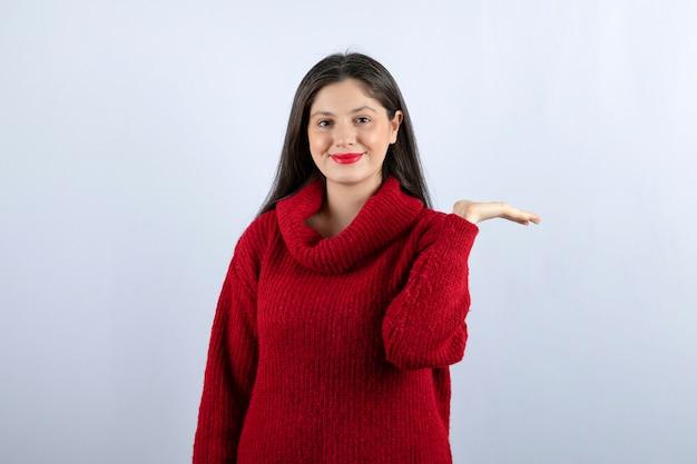 Immagine di una giovane donna in maglione rosso che mostra la mano su sfondo bianco white