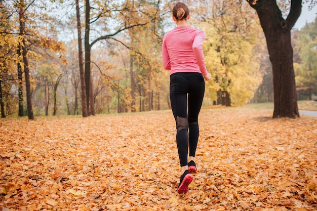 Picture of young woman running in park. it is chilly weather outside. orange leaves lying on ground. young woman jogging. she run alone.