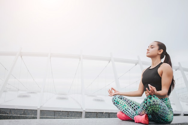 Picture of young woman sitting in lotus position and meditating