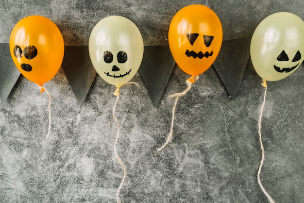 Pictured balloons in halloween style with black flags hanging on grey background