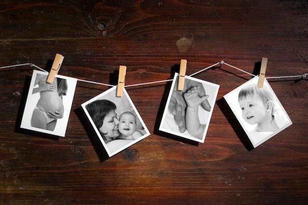 Фотографии новорожденного и мамы, прикрепленные к веревке с вращением одежды на деревянном фоне